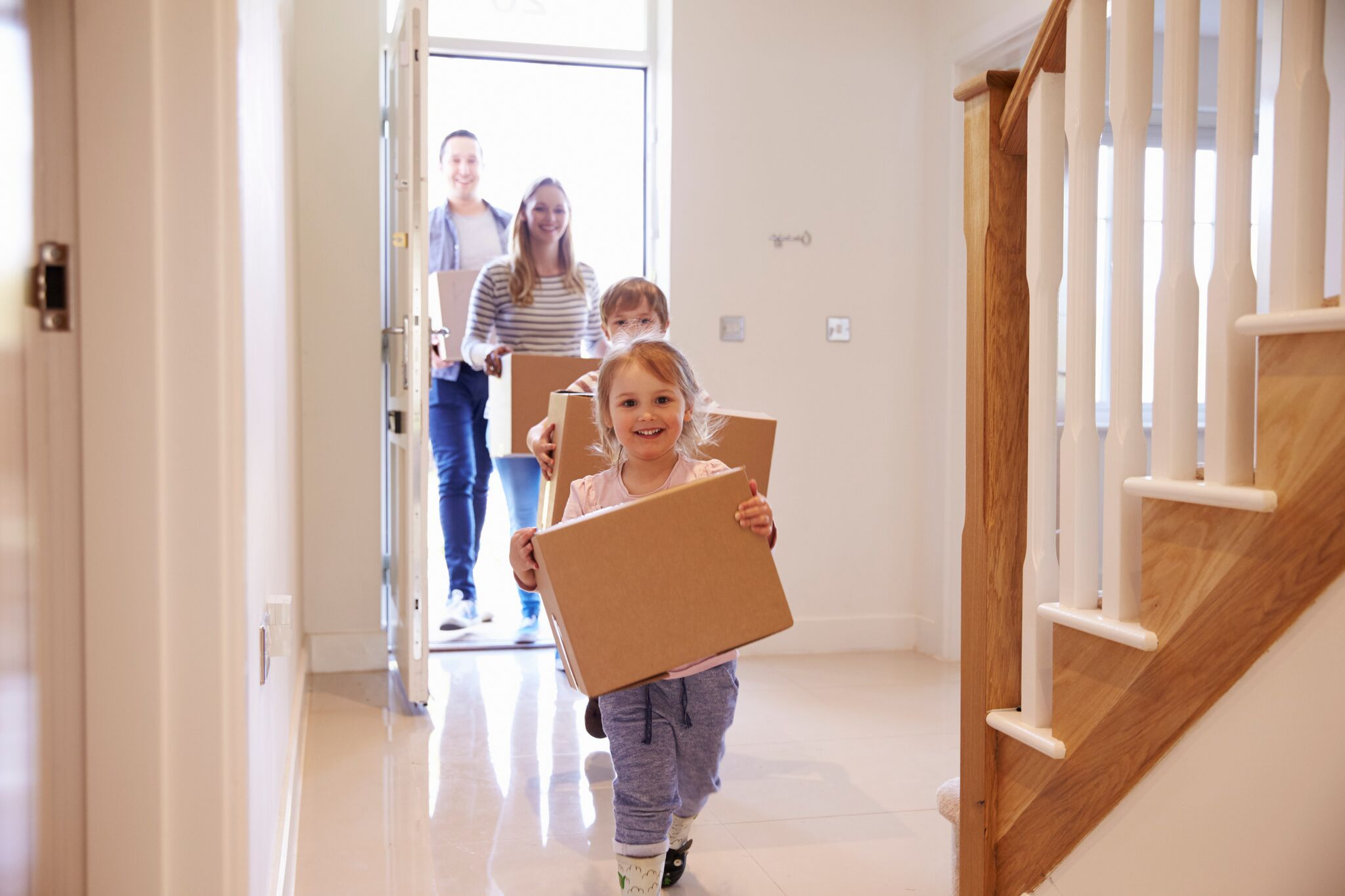 family carrying boxes into home