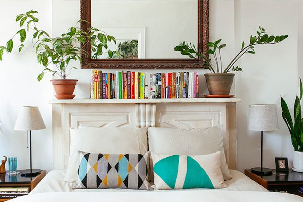 an organized shelf with a line of books and plants on top, inside a bedroom