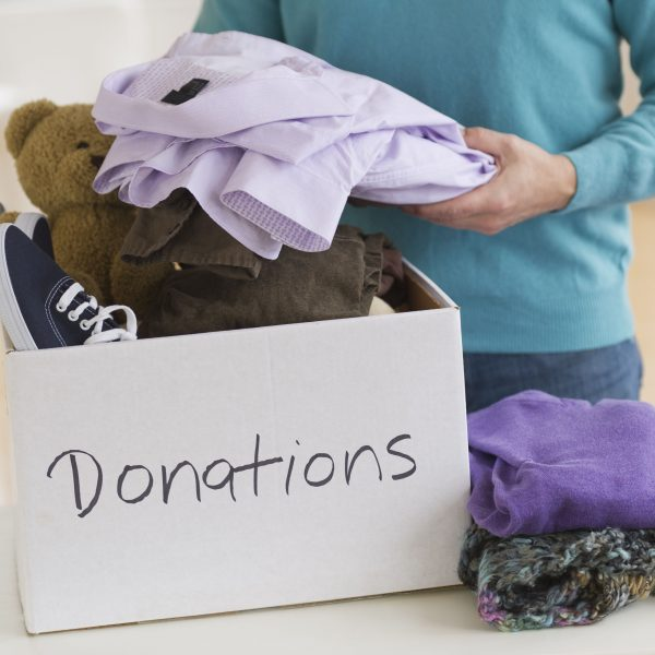 woman putting clothes inside a donations box