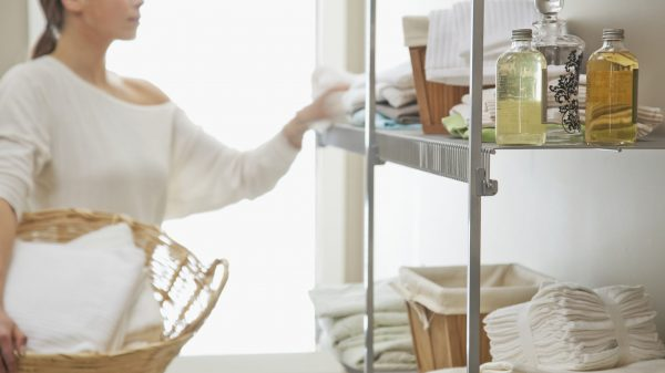 woman carrying a basket while organizing laundry storage