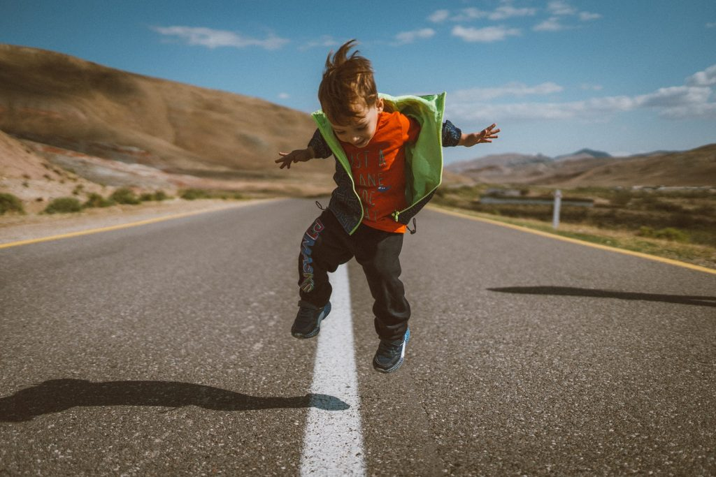 child jumping on road