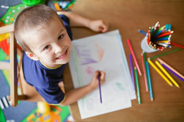 a boy happily showing off his drawing