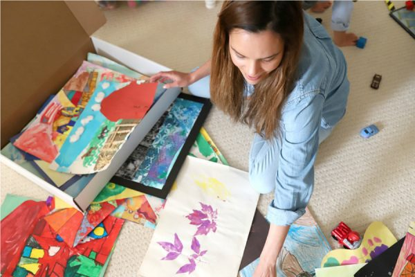 a mother storing her kids artwork in a flat cardboard box